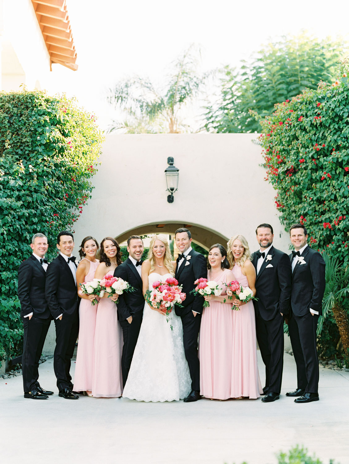 Bridal party portrait of bridesmaids in pink dresses and groomsmen in black tuxedos and bride wearing a lace Watters sweetheart gown with large bridal bouquet of pink tones with peonies and roses. Miramonte Resort wedding. Film photography by Cavin Elizabeth.