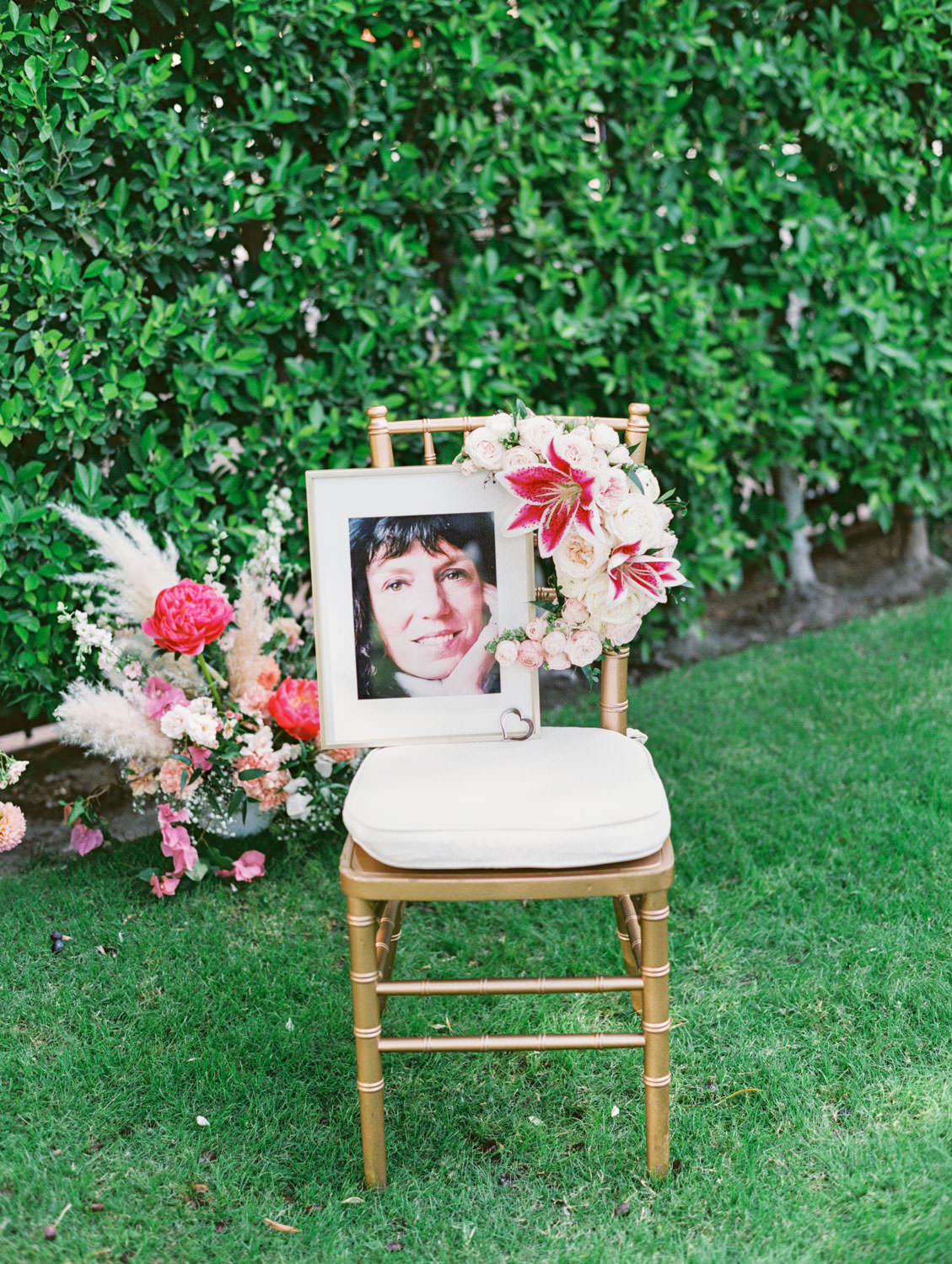 Framed portrait of the bride's deceased mother sitting on a chiavari chair with floral arrangements. Film photography by Cavin Elizabeth.