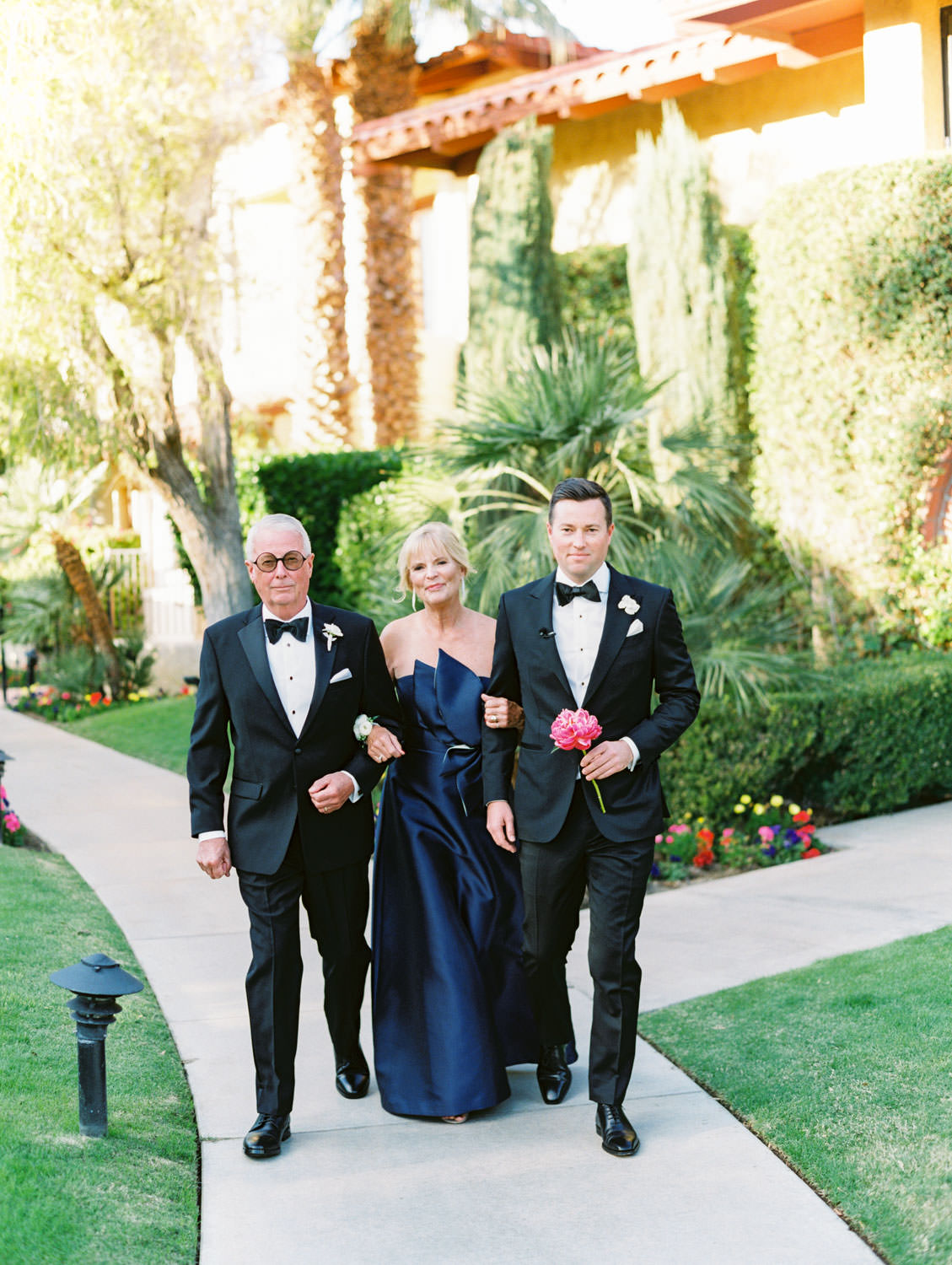 Groom walking down the aisle with his parents. Mother of the bride in a satin navy gown. Miramonte Resort ceremony on Miramonte Green. Film photography by Cavin Elizabeth.