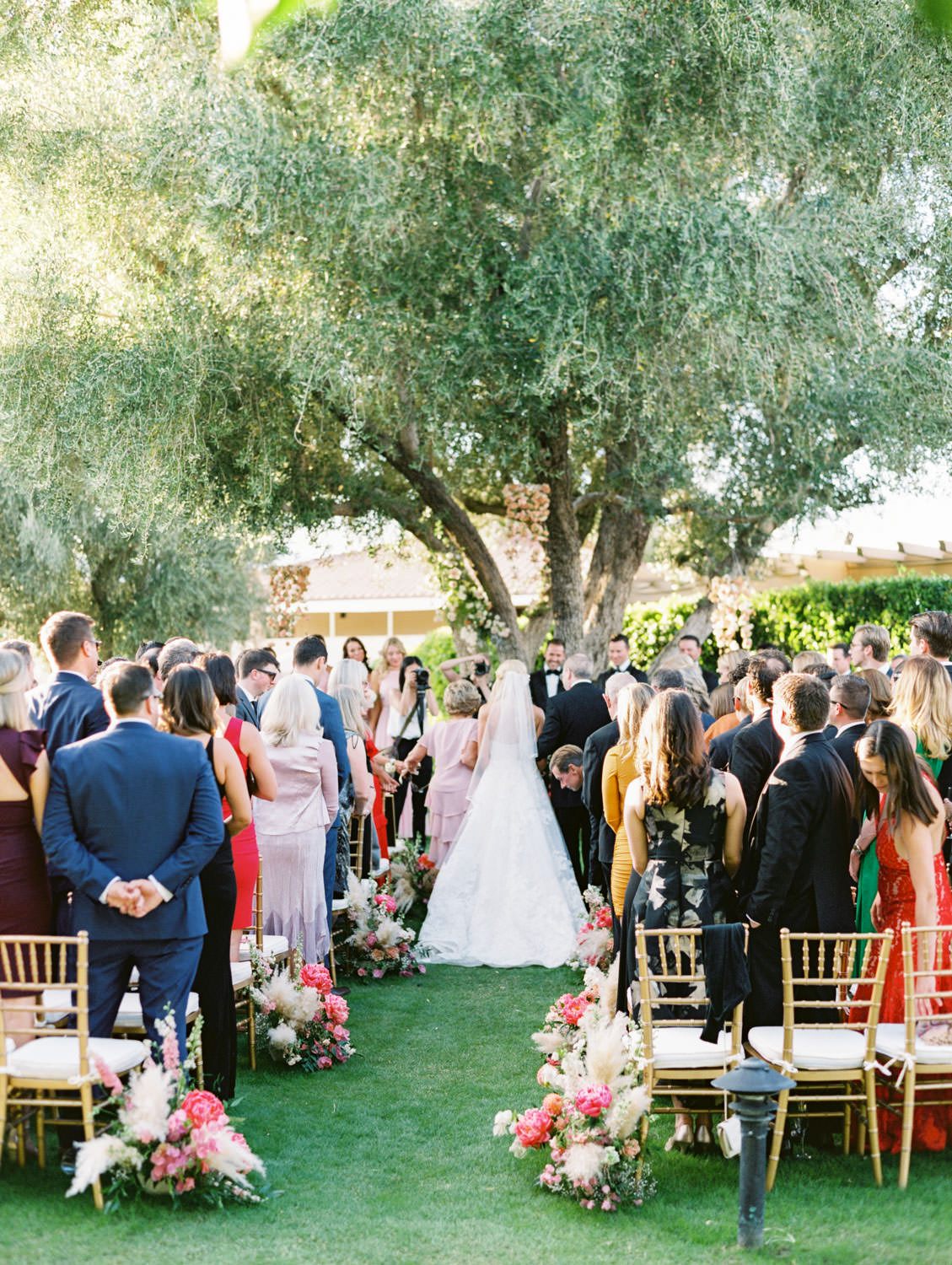 Large tree with hanging floral arrangements and pink peonies and pampas grass along the aisle. Miramonte Resort ceremony on Miramonte Green. Film photography by Cavin Elizabeth.