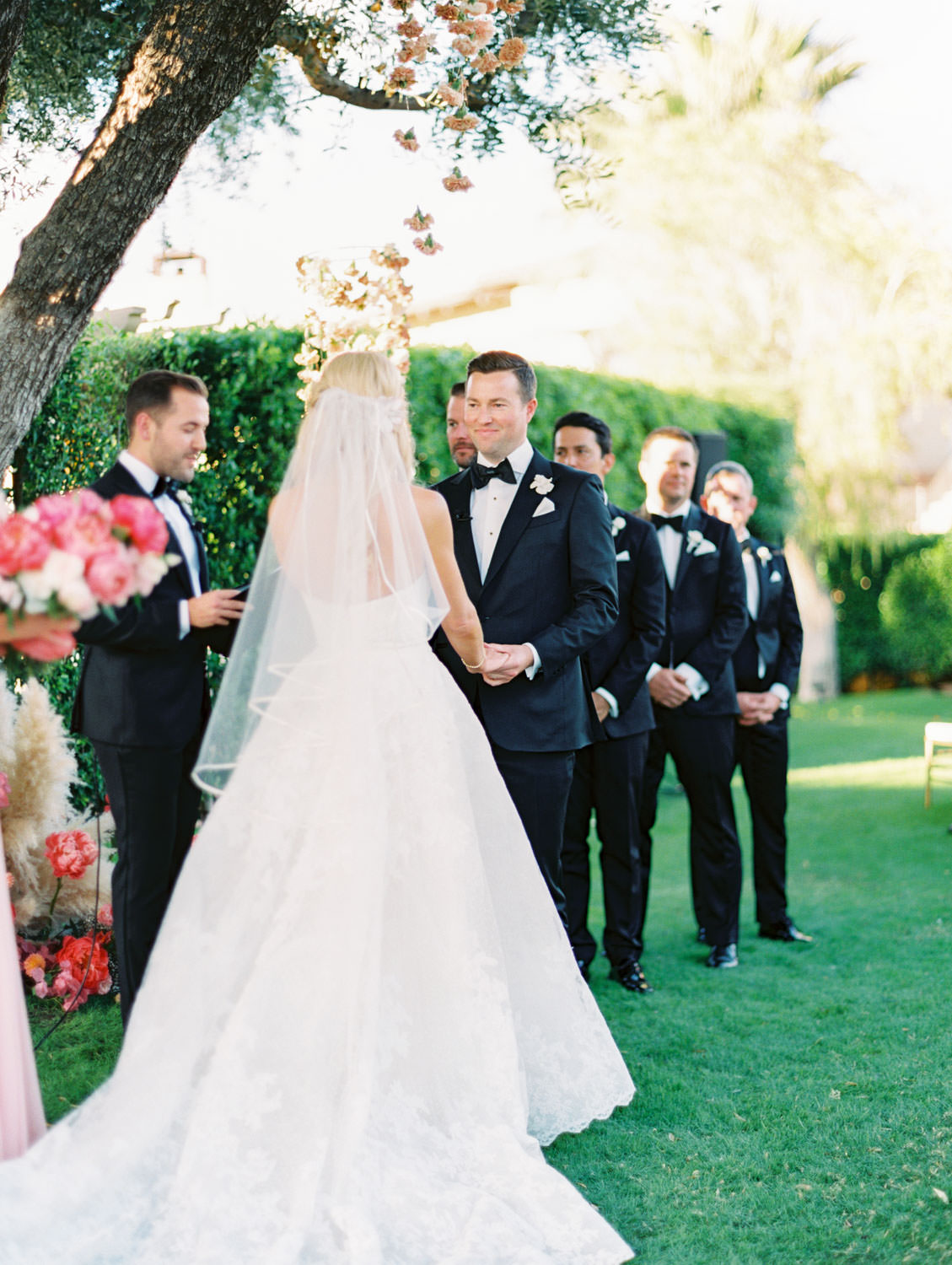 Groom smiling at the bride during the wedding ceremony. Miramonte Resort ceremony on Miramonte Green. Film photography by Cavin Elizabeth.