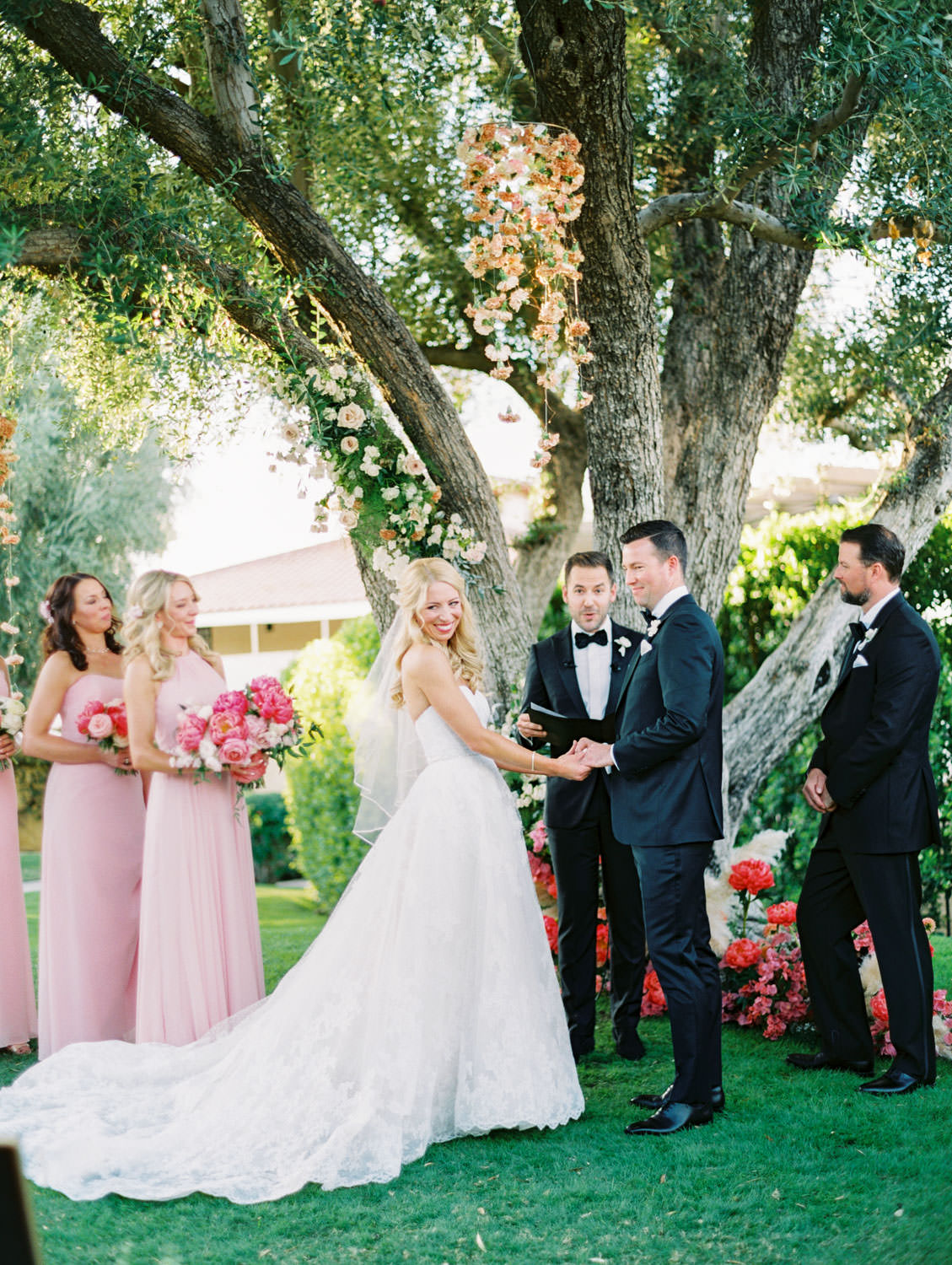Bride and groom smiling during the ceremony. Large tree with hanging floral arrangements and pink peonies and pampas grass spiraling up the trunk. Miramonte Resort ceremony on Miramonte Green. Film photography by Cavin Elizabeth.