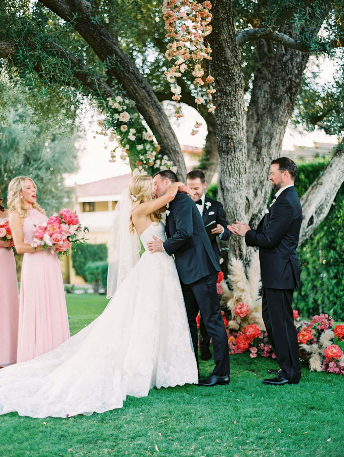 Bride and groom first kiss. Large tree with hanging floral arrangements and pink peonies and pampas grass spiraling up the trunk. Miramonte Resort ceremony on Miramonte Green. Film photography by Cavin Elizabeth.