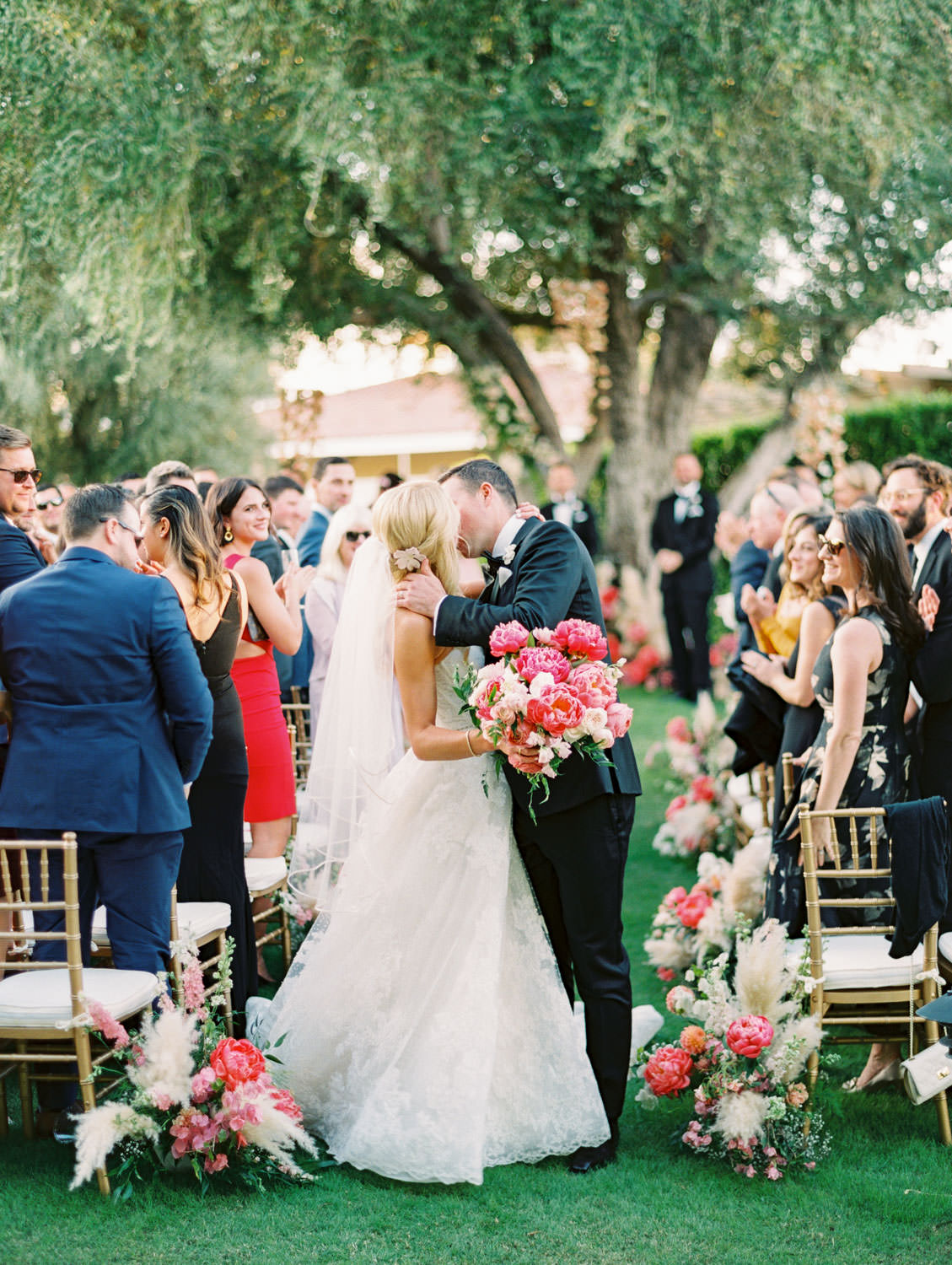 Bride and groom kissing at the end of the aisle. holding a pink bouquet. Large tree with hanging floral arrangements and pink peonies and pampas grass spiraling up the trunk. Miramonte Resort ceremony on Miramonte Green. Film photography by Cavin Elizabeth.