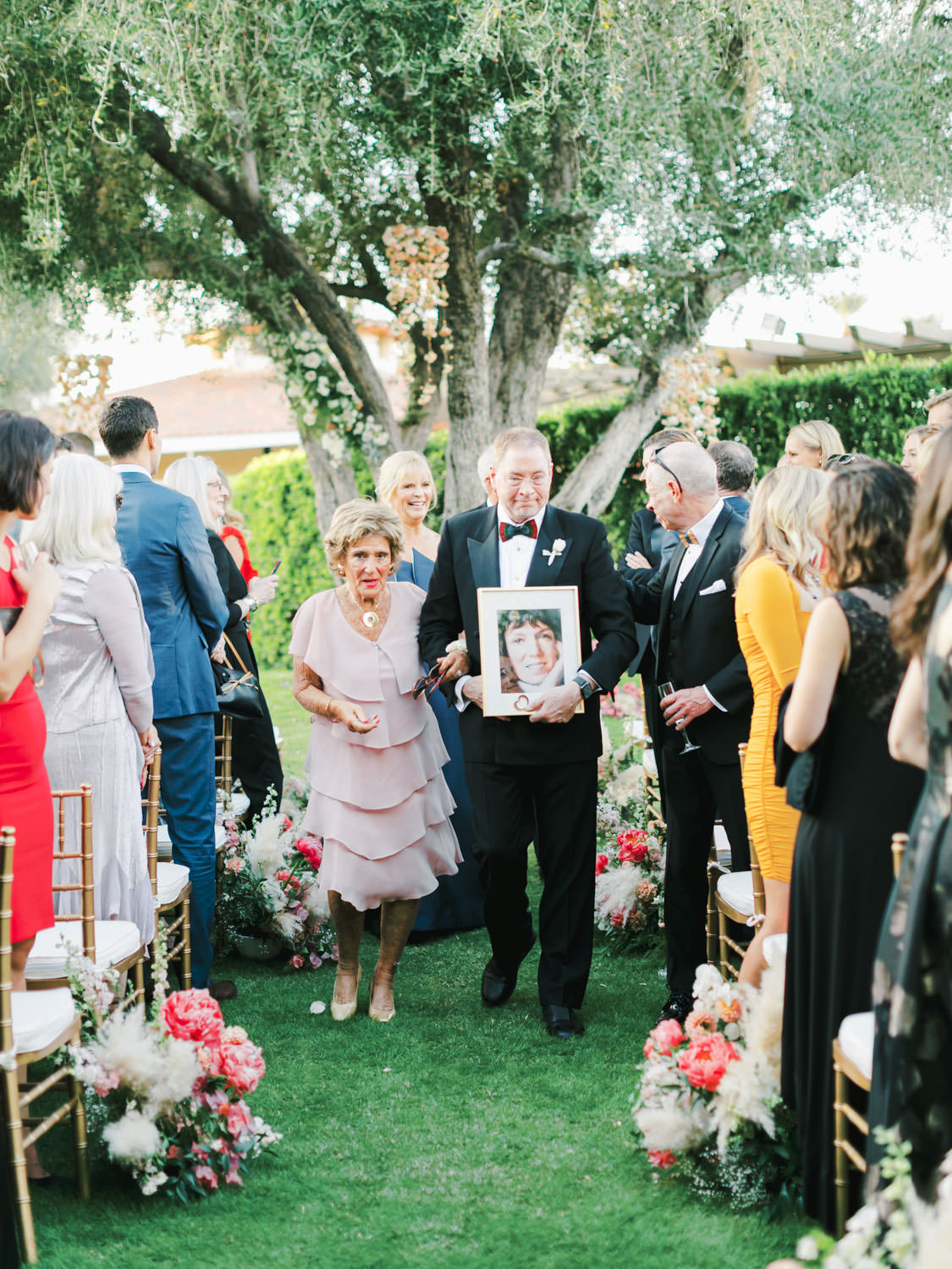 Father of the bride walking down the aisle carrying a framed portrait of the bride's deceased mother in her honor. Miramonte Resort ceremony on Miramonte Green. Film photography by Cavin Elizabeth.