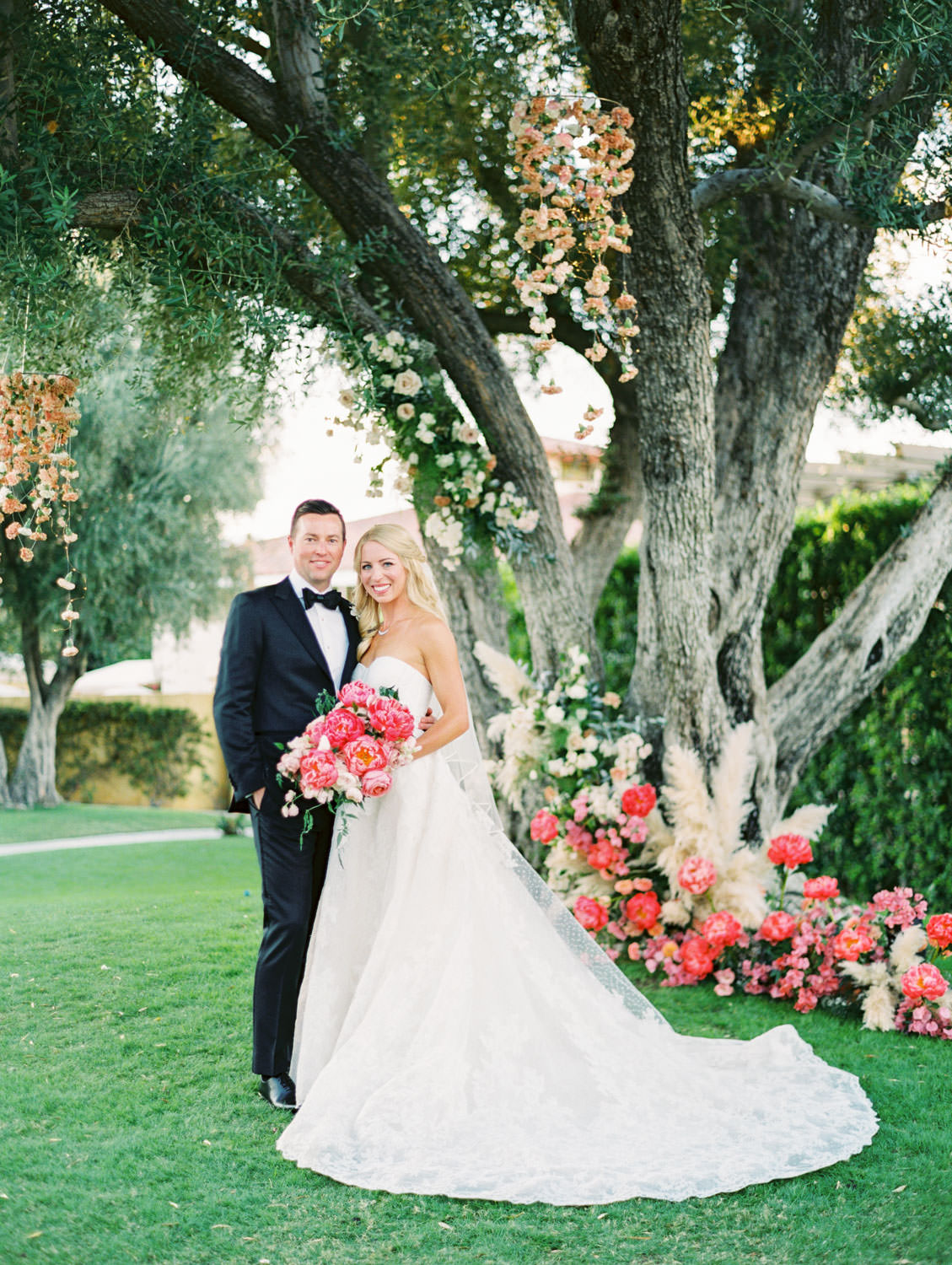 Bride and groom smiling at the camera. Bride in lace Watters gown holding a pink bouquet. Large tree with hanging floral arrangements and pink peonies and pampas grass spiraling up the trunk. Miramonte Resort ceremony on Miramonte Green. Film photography by Cavin Elizabeth.
