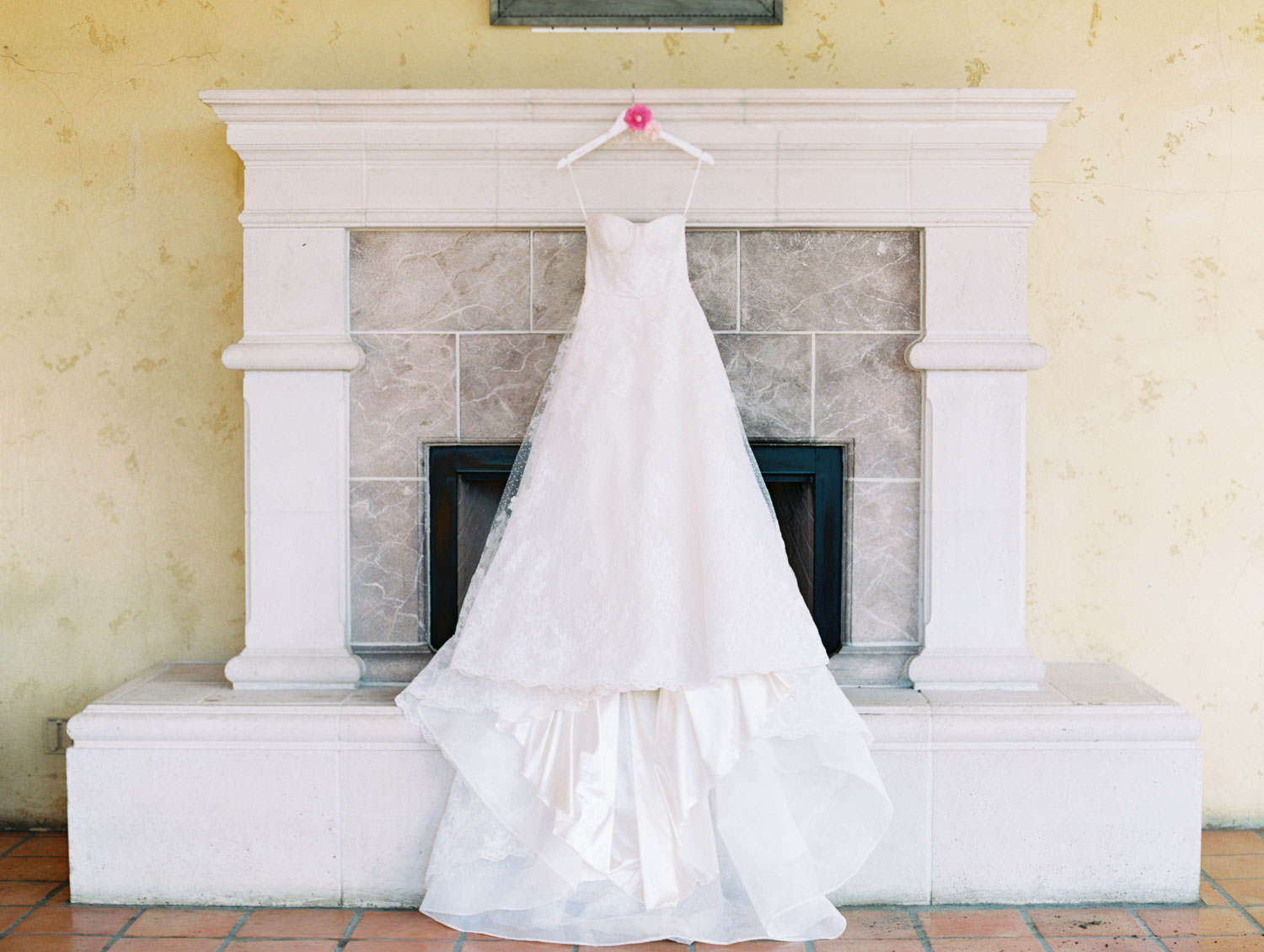 Watters lace sweetheart neckline wedding gown on a custom hanger adorned with pink flowers. Miramonte Resort wedding. Film photography by Cavin Elizabeth.