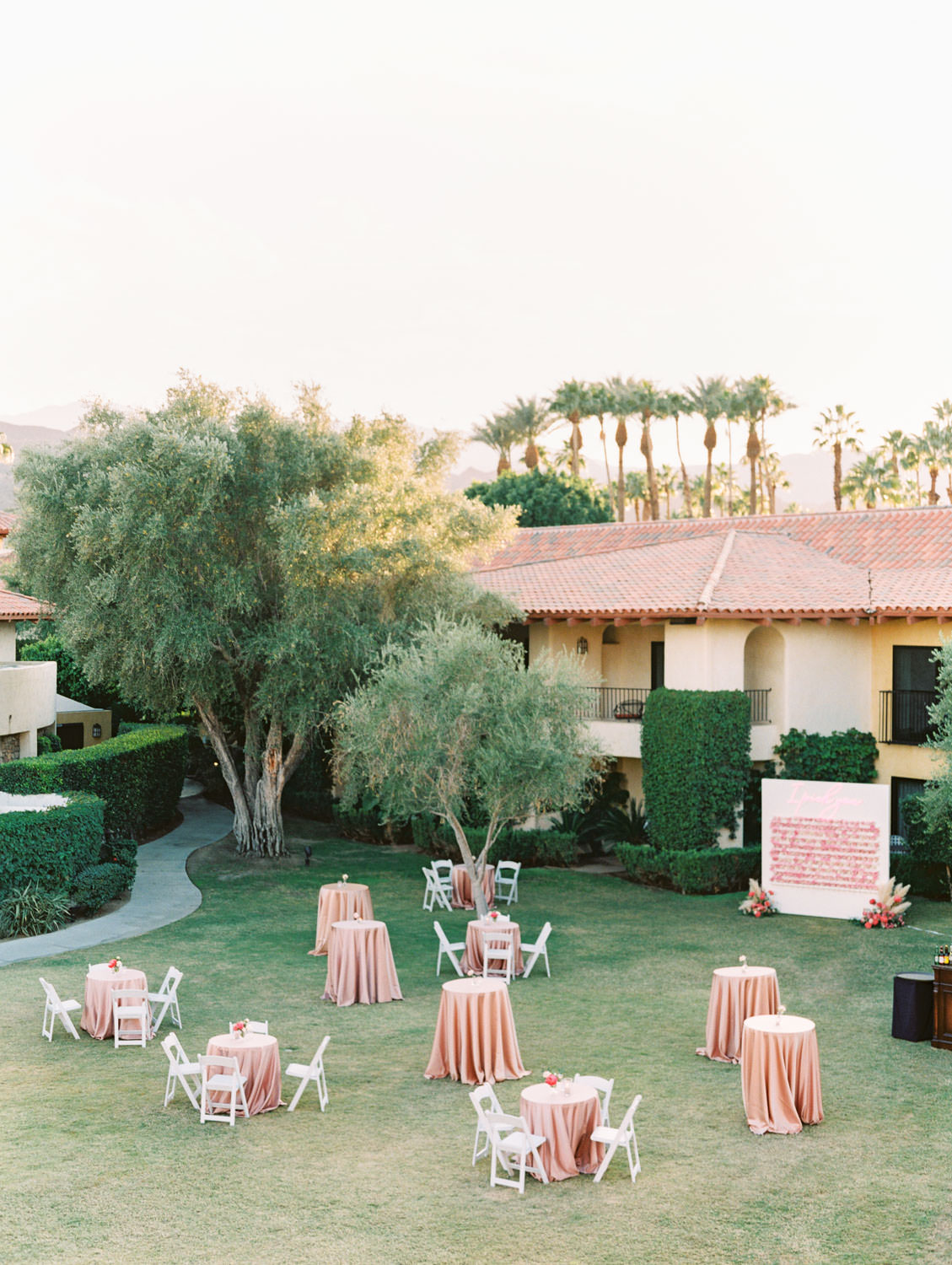 Cocktail hour on a grassy lawn with pink linens on tables. Miramonte Resort wedding. Film photography by Cavin Elizabeth.