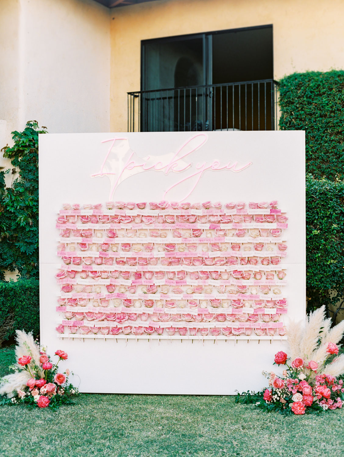 "White escort display with neon ""I pick you"" sign and each guest's escort card comes with a pink rose to pick off of the wall. Board surrounded by arrangements of pink peonies, roses, and pampas grass. Miramonte Resort wedding. Film photography by Cavin Elizabeth."