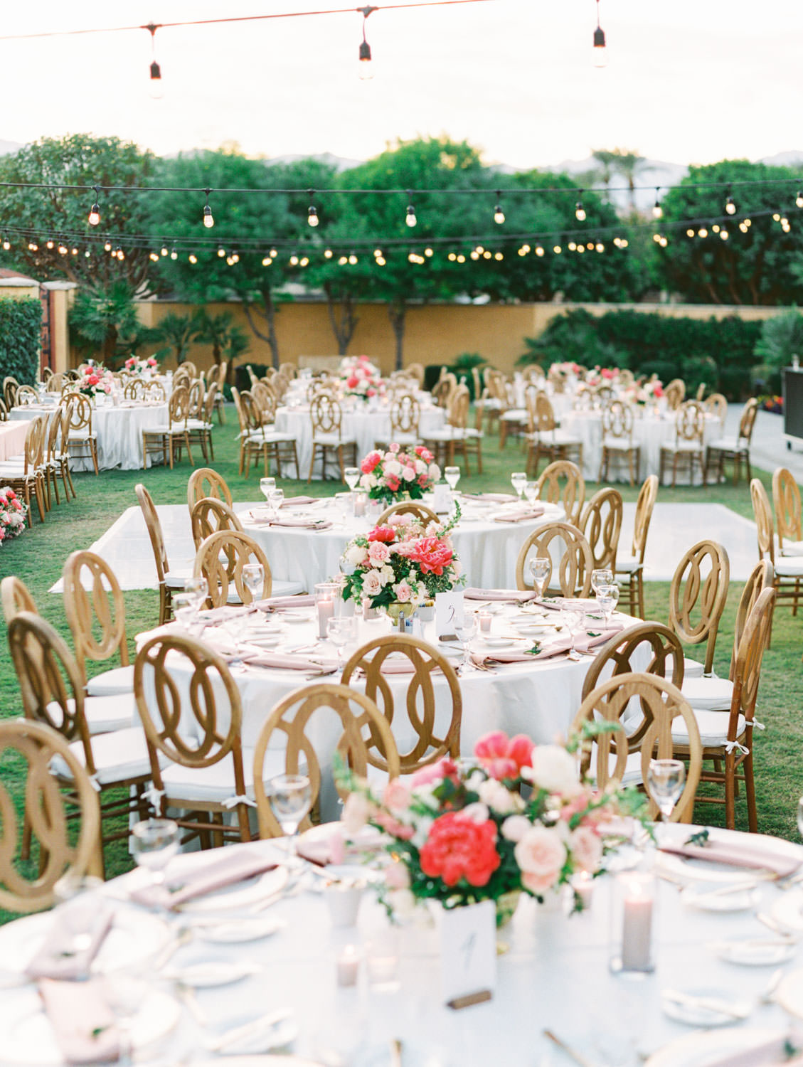 Above view of the entire wedding reception with round tables and oak Orion chairs. White dance floor and market lights. Pink and ivory bold centerpieces with peonies and roses. Miramonte Resort reception on the Mesquite Lawn. Film photography by Cavin Elizabeth.