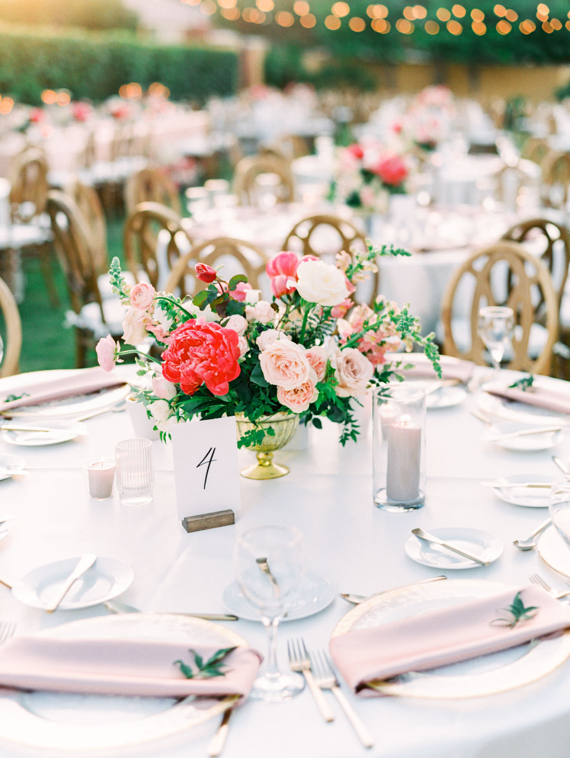 Round table with ivory linen and blush napkins on clear gold rimmed chargers. Pink and ivory bold centerpieces with peonies, sweet peas, ivy, and roses. Miramonte Resort reception on the Mesquite Lawn. Film photography by Cavin Elizabeth.