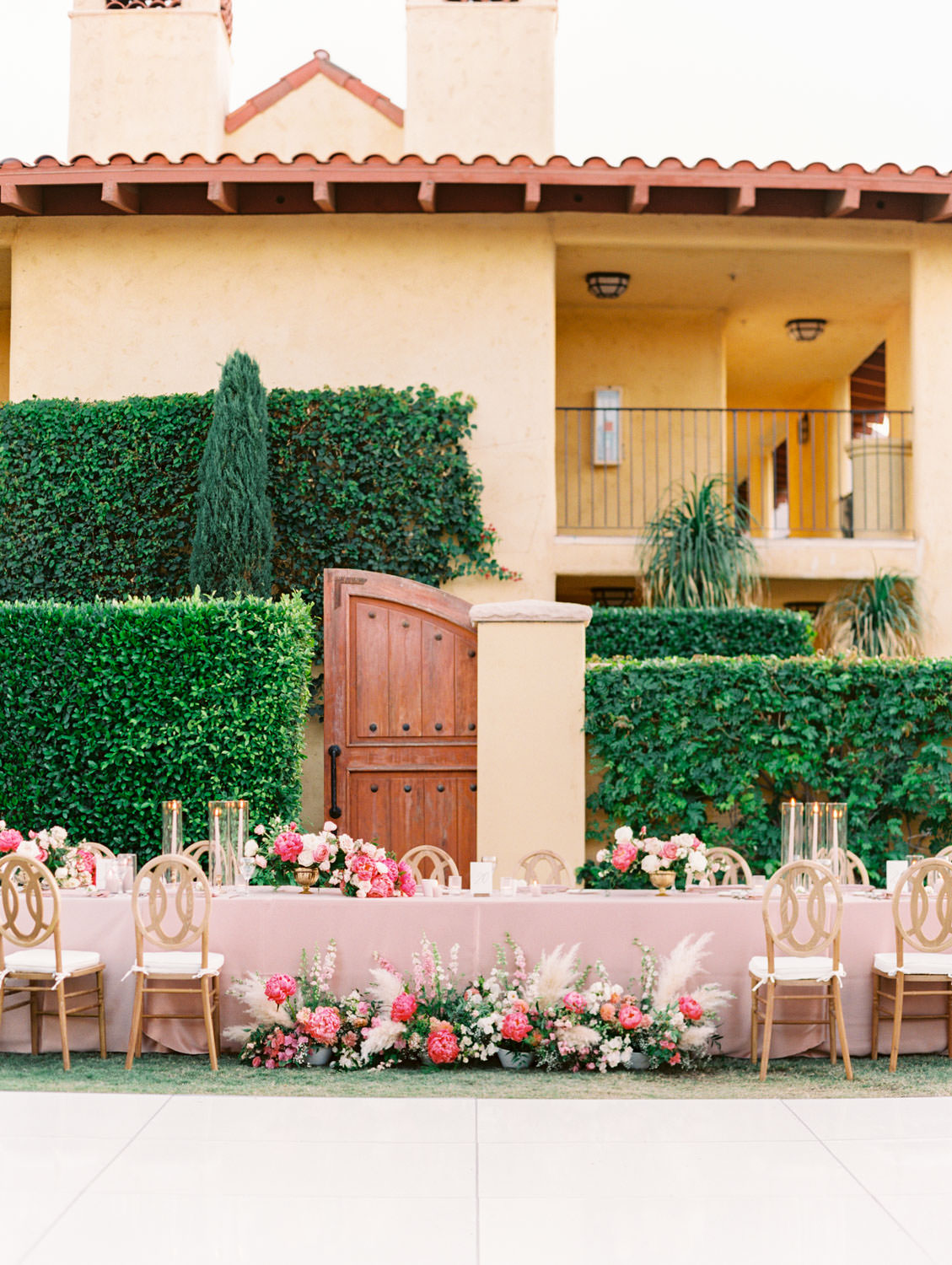 Long table for head table with pink linens and oak Orion chairs. Candles in hurricanes and pampas grass and peony arrangements in front of the bride and groom seats. Pink and ivory bold centerpieces with peonies, sweet peas, ivy, and roses. Miramonte Resort reception on the Mesquite Lawn. Film photography by Cavin Elizabeth.