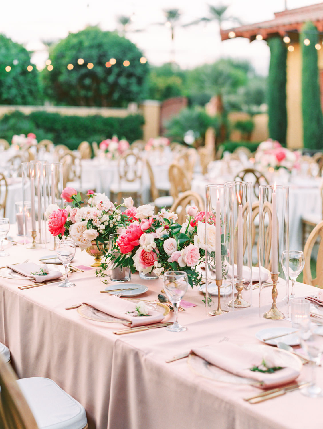 Long table for head table with pink linens and oak Orion chairs. Candles in hurricanes. Pink and ivory bold centerpieces with peonies, sweet peas, ivy, and roses. Miramonte Resort reception on the Mesquite Lawn. Film photography by Cavin Elizabeth.
