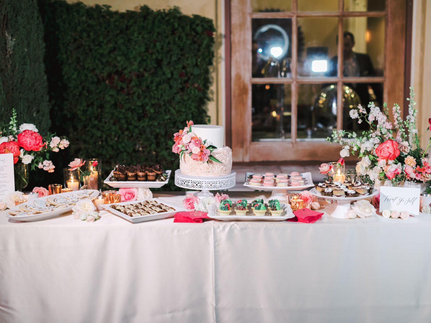 Dessert display on pink linens with various small desserts like cookies and cupcakes. Two tier wedding cake with blush floral icing on bottom and white top tier with cascading pink and ivory flowers. photography by Cavin Elizabeth.