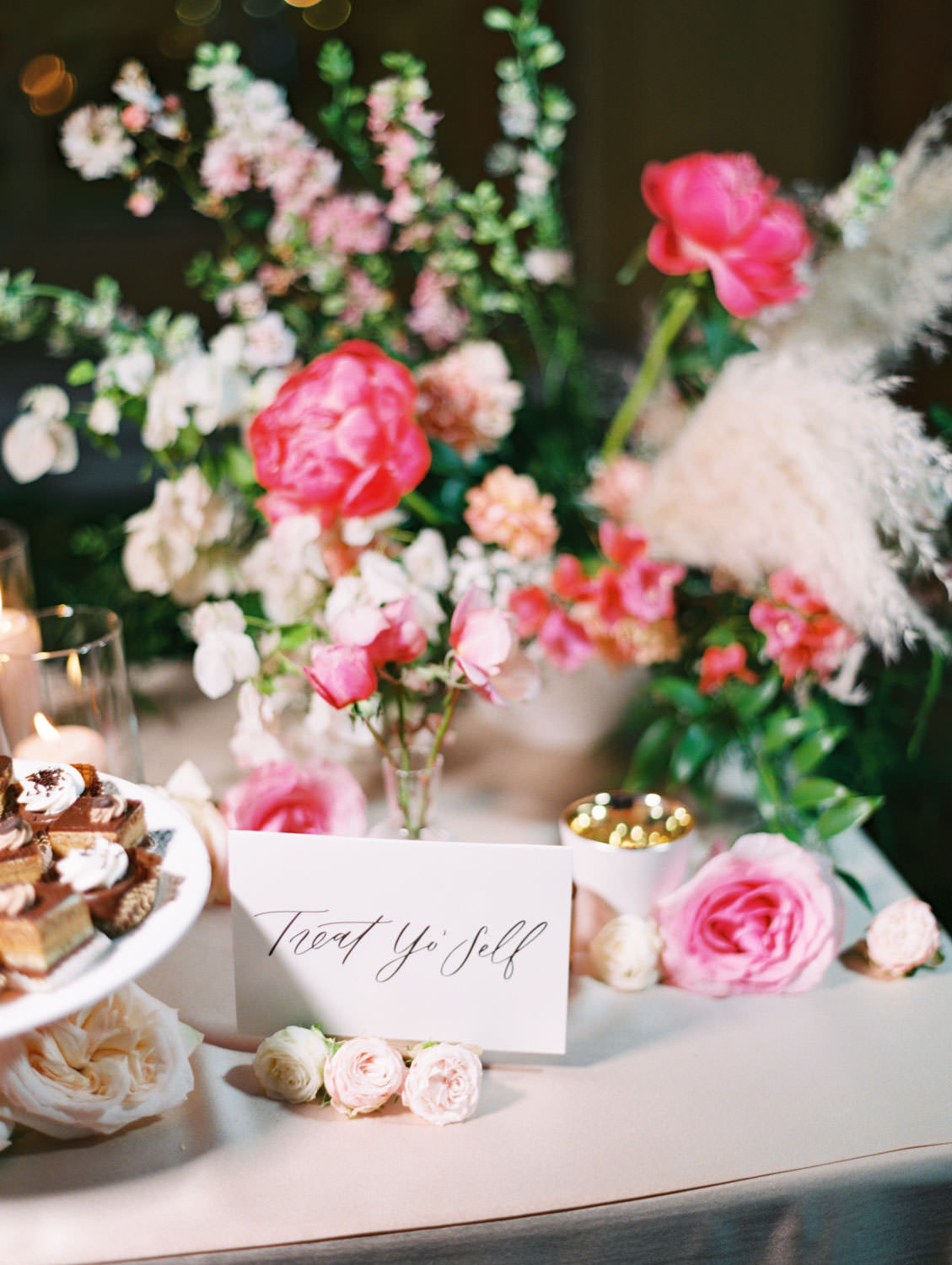 Dessert display treat yo'self sign with arrangement of pink and ivory flowers. Film photography by Cavin Elizabeth.
