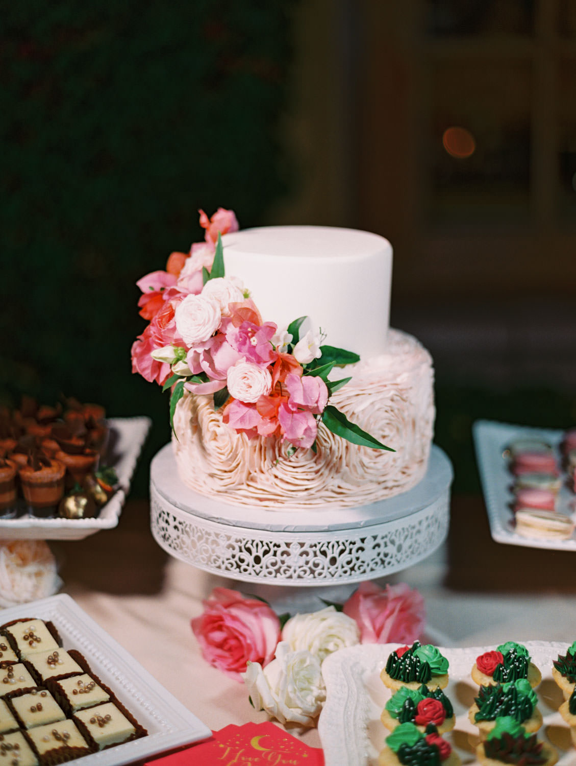 Dessert display on pink linens with various small desserts like cookies and cupcakes. Two tier wedding cake with blush floral icing on bottom and white top tier with cascading pink and ivory flowers. Film photography by Cavin Elizabeth.