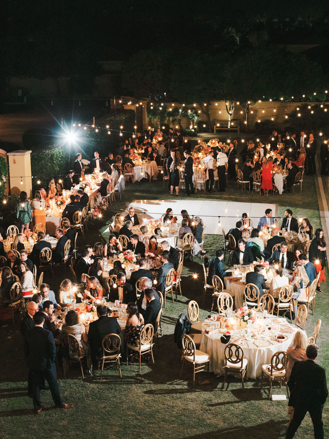 Above view of the entire reception with market lights and round tables with oak Orion chairs. Miramonte Resort wedding reception. Photography by Cavin Elizabeth.