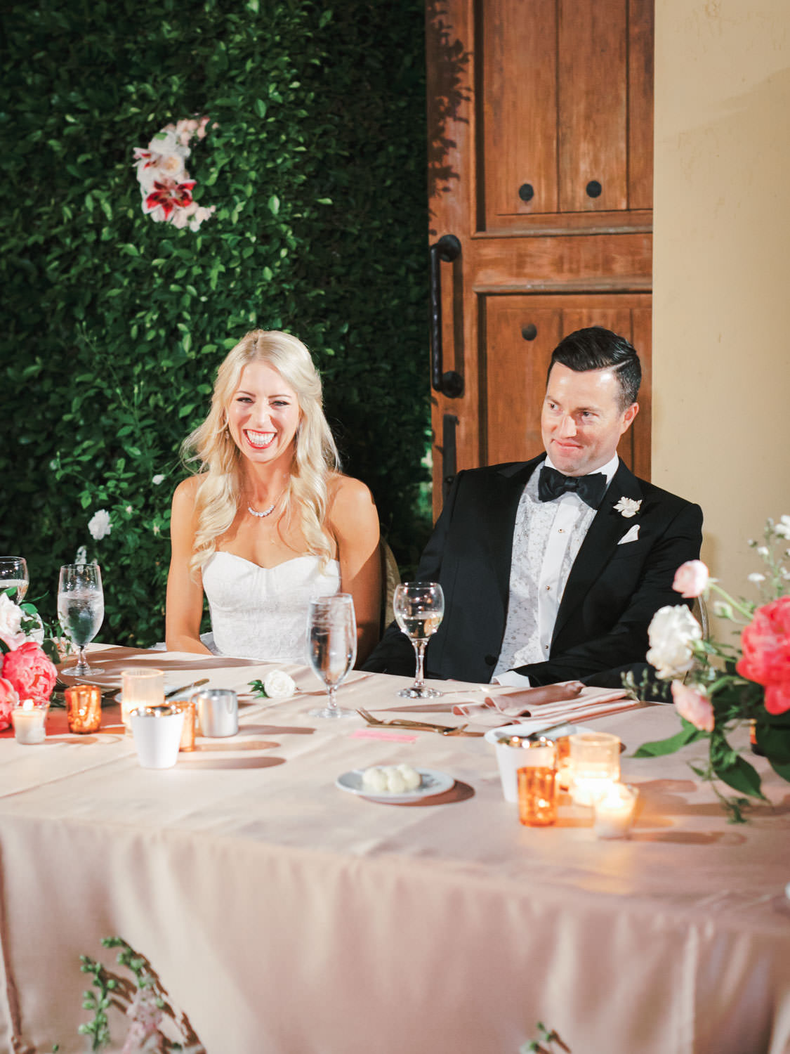 Bride and groom laughing at toasts. Miramonte Resort wedding reception. Photography by Cavin Elizabeth.