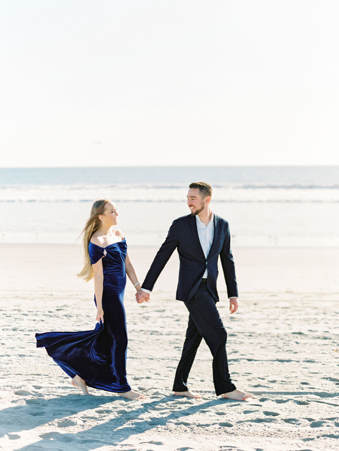 Bride in navy velvet gown and groom in suit. Elegant Coronado Engagement Photos on the Beach on film by Cavin Elizabeth Photography.