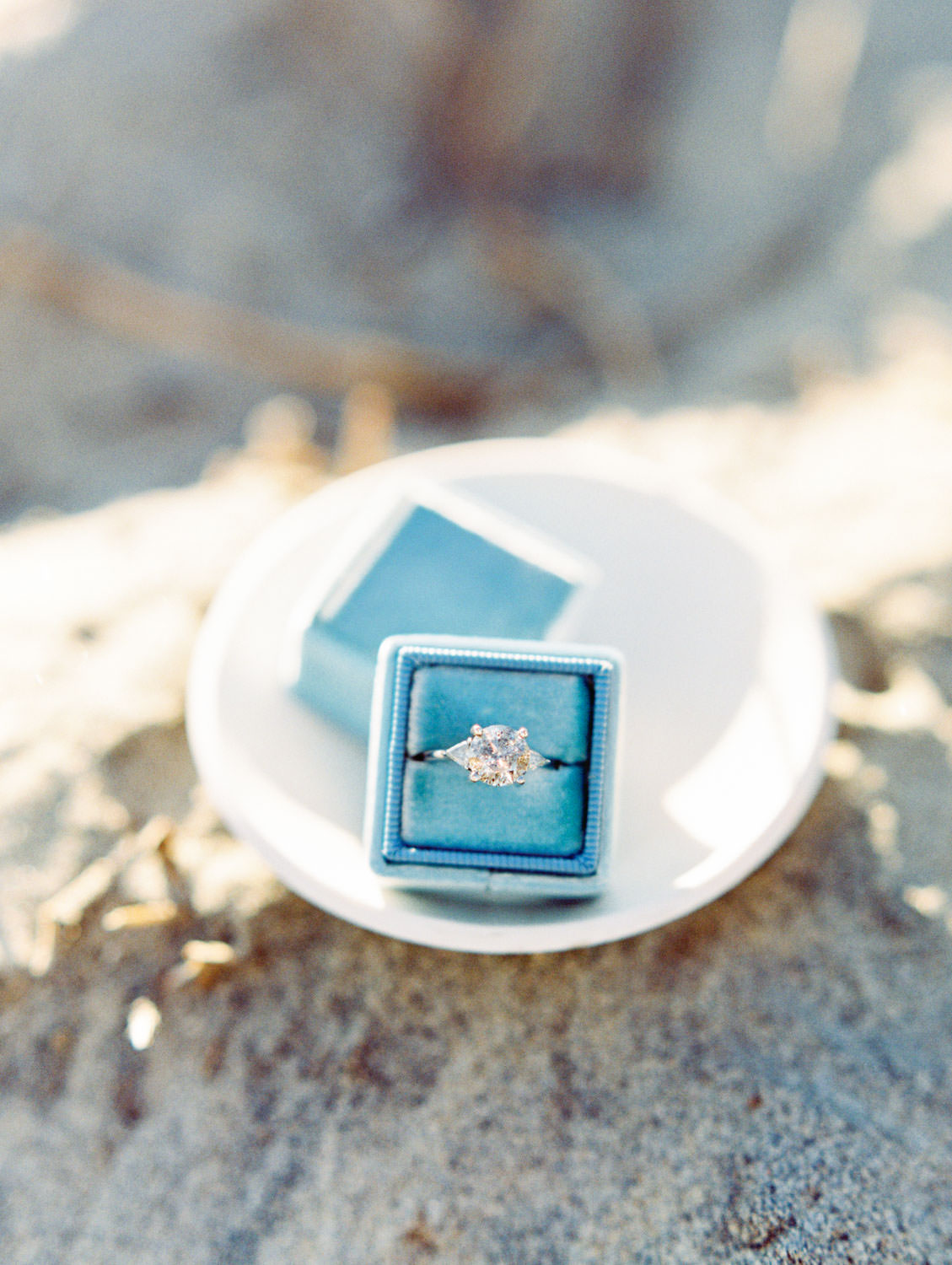 Cushion cut engagement ring in an ocean blue velvet Mrs box ring box on top of a porcelain dish on the sand on film by Cavin Elizabeth Photography.