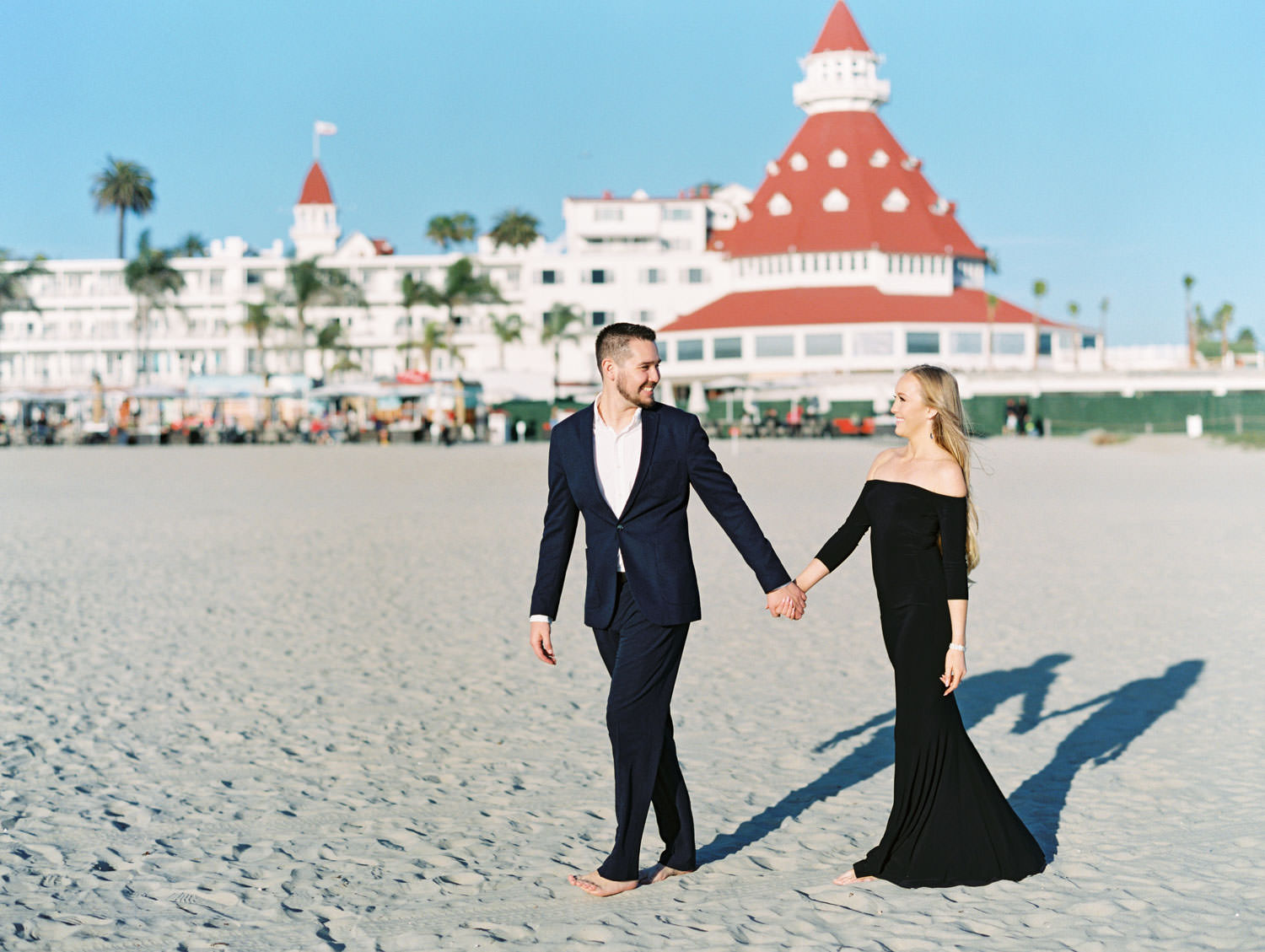 Bride in black off shoulder long sleeve gown and groom in suit. Hotel Del Coronado Engagement Photos on the Beach on film by Cavin Elizabeth Photography.