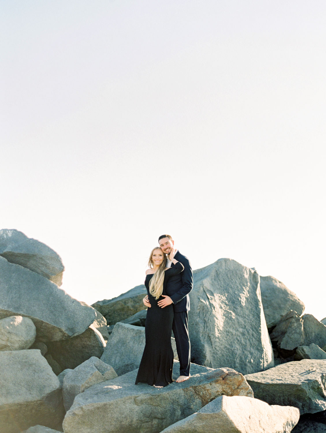 Bride in black off shoulder long sleeve gown and groom in suit. Hotel Del Coronado Engagement Photos on the rock pile on film by Cavin Elizabeth Photography.