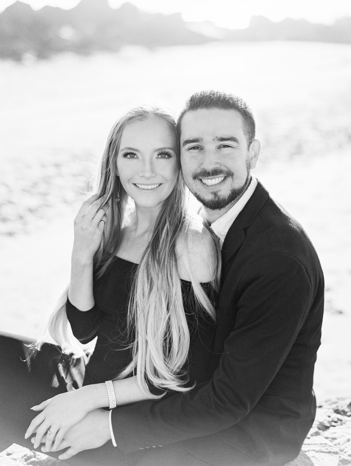 Black and white photo of Bride in black off shoulder long sleeve gown and groom in suit. Hotel Del Engagement Photos on film by Cavin Elizabeth Photography.