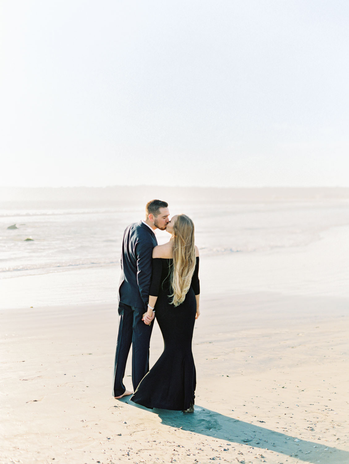 Bride in black off shoulder long sleeve gown and groom in suit. Hotel Del Coronado Engagement Photos on the beach pile on film by Cavin Elizabeth Photography.