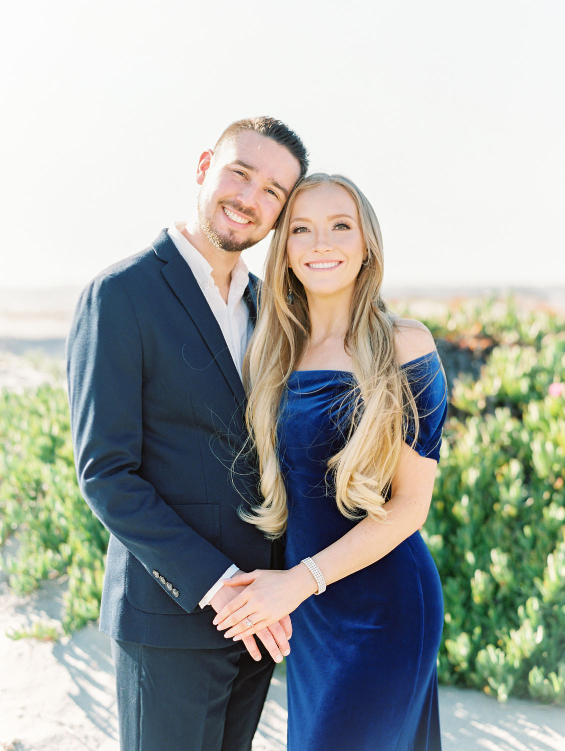 Bride in navy velvet gown and groom in suit. Elegant Coronado Island Engagement Photos on the Beach on film by Cavin Elizabeth Photography.