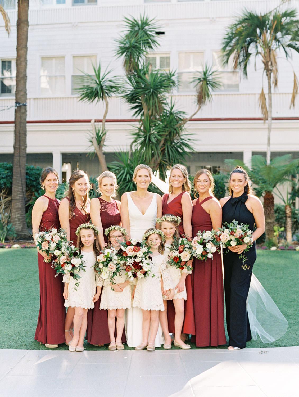 Bride in BHLDN Jenny Yoo sleeveless wedding dress with bridesmaids in burgundy dresses and flower girls in ivory dresses with flower crowns. Hotel Del Coronado Wedding on film by Cavin Elizabeth.