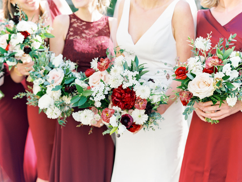 Bride in BHLDN Jenny Yoo sleeveless wedding dress with bridesmaids in burgundy dresses. Bridal bouquets with burgundy, ivory, blush, and greenery. Hotel Del Coronado Wedding on film by Cavin Elizabeth.