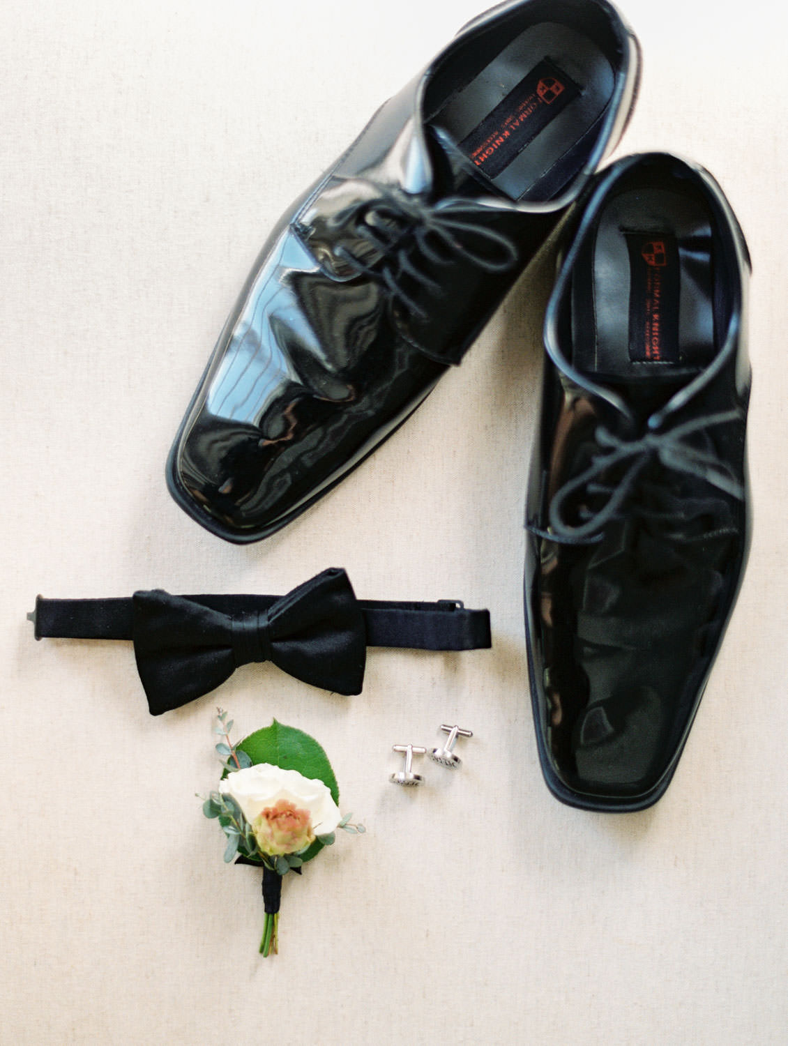 Groom's black tux shoes, bowtie, white rose and greenery boutonniere and silver monogram cufflinks. Cavin Elizabeth Photography