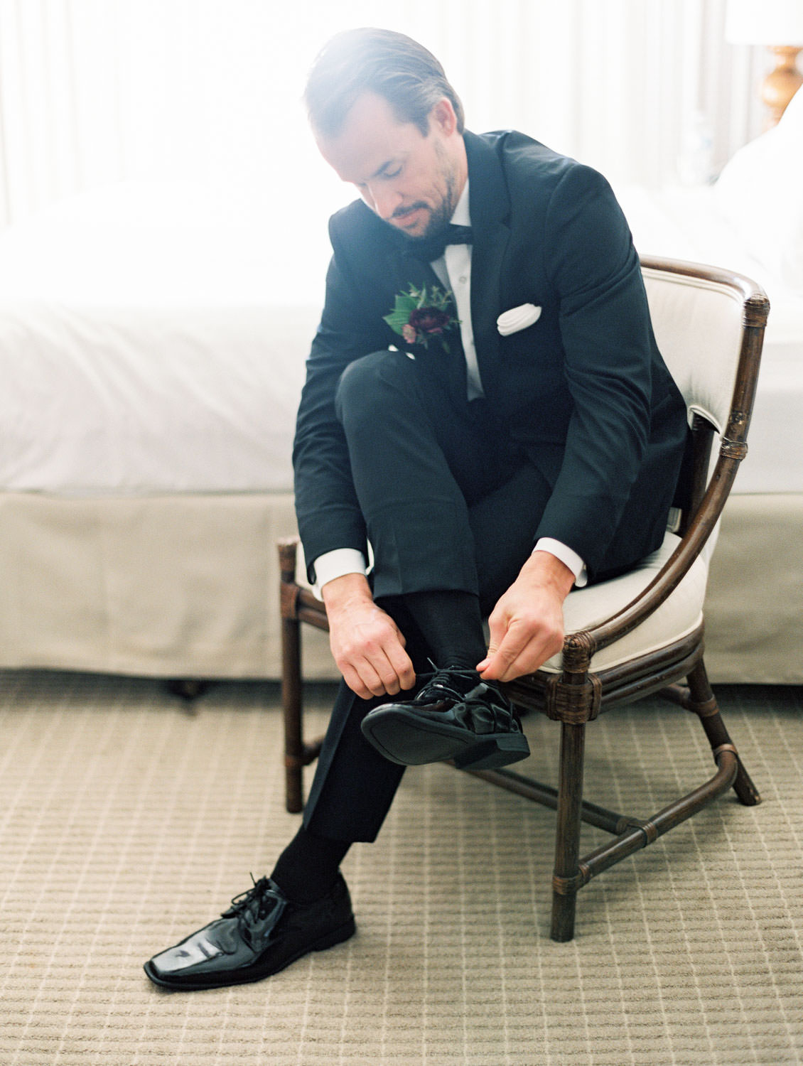 Groom putting on shoes with burgundy boutonniere with greenery and black tuxedo on film by Cavin Elizabeth Photography.