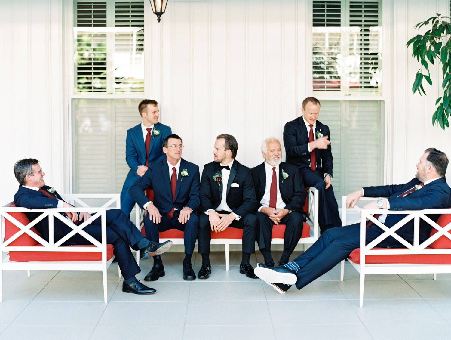 Groom in black tuxedo and groomsmen in navy suits with burgundy ties hanging out on red and white chairs at the Hotel Del. Cavin Elizabeth Photography.