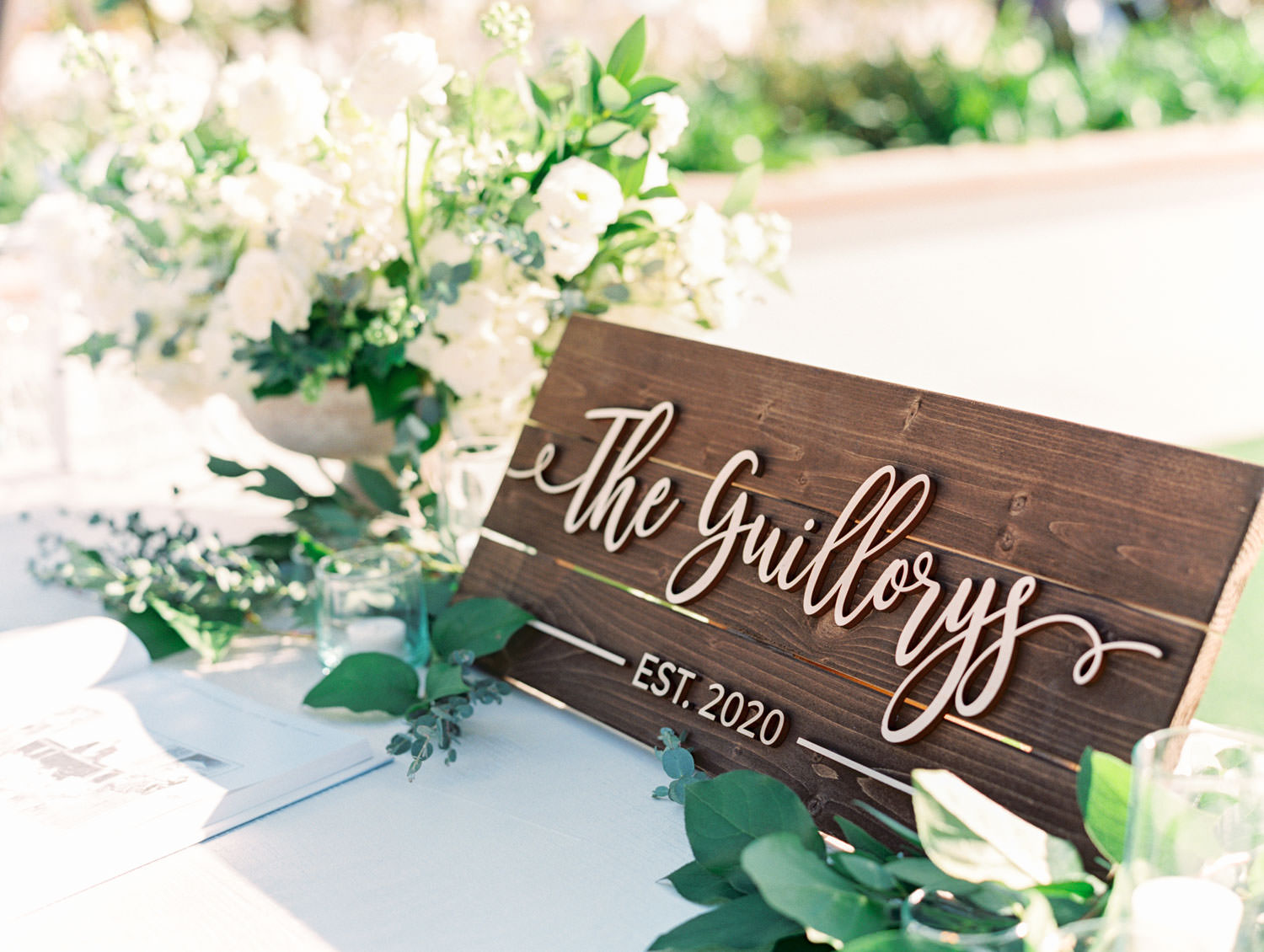 Wedding welcome table with ivory and green arrangement and wooden signs. Hotel Del Coronado wedding on film by Cavin Elizabeth.