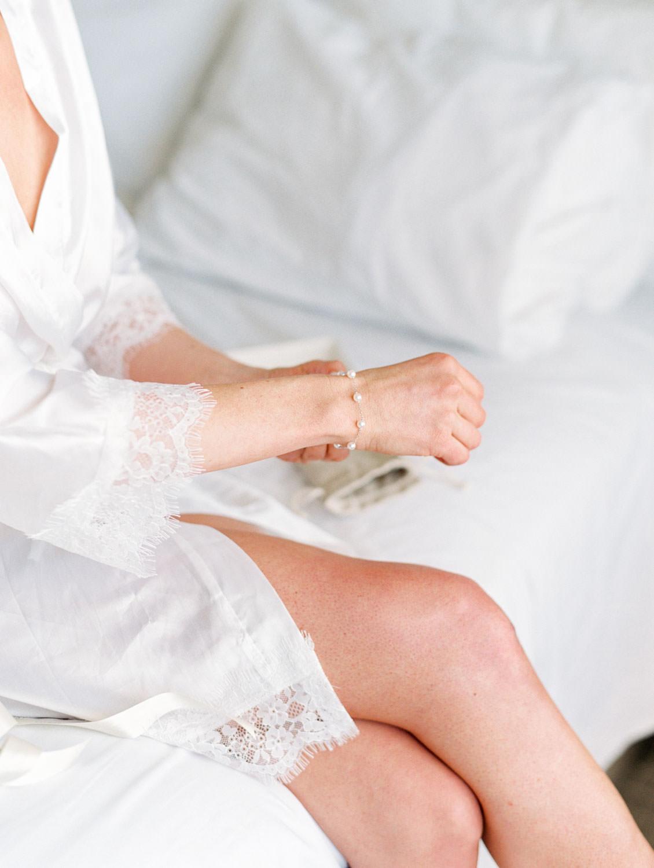 Bride putting on pearl bracelet gift from the groom. Hotel Del Coronado Wedding on film by Cavin Elizabeth.