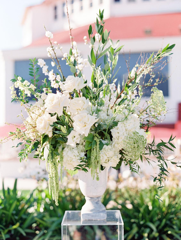 Outdoor terrace ceremony with ivory and green aisle arrangements. Hotel Del Coronado wedding on film by Cavin Elizabeth.