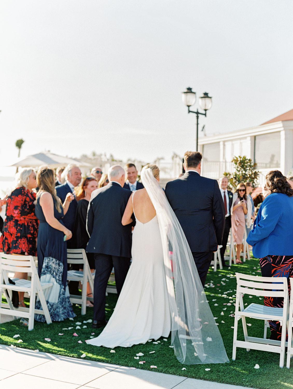 Bride walking down the aisle with a long veil. Hotel Del Coronado wedding on film by Cavin Elizabeth.
