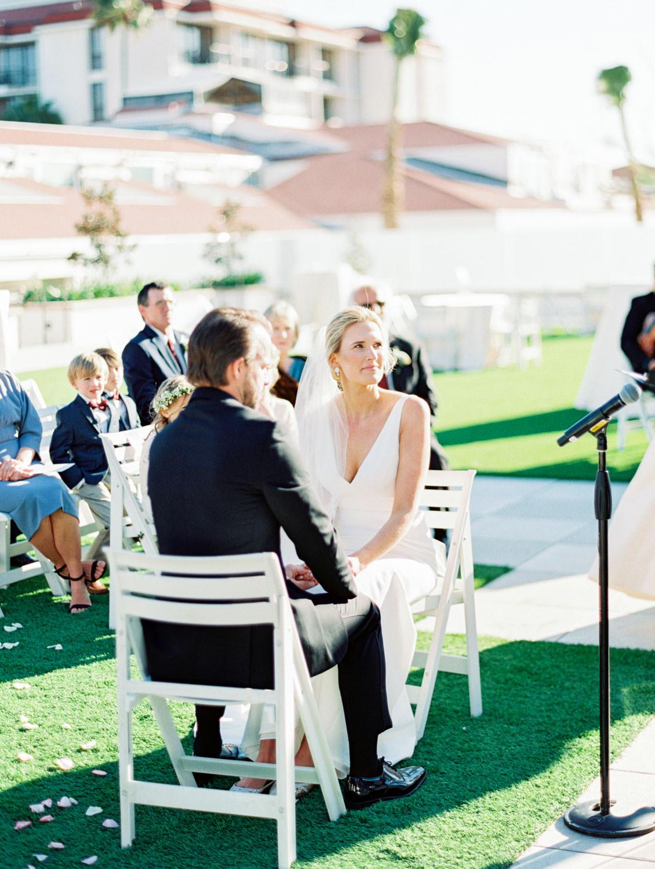 Bride and groom sitting for the wedding ceremony. Hotel Del Coronado wedding on film by Cavin Elizabeth.