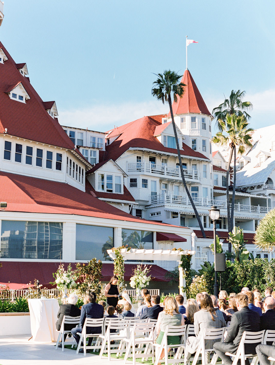 Ceremony with a view of the iconic hotel Del red roofs. Hotel Del Coronado wedding on film by Cavin Elizabeth.