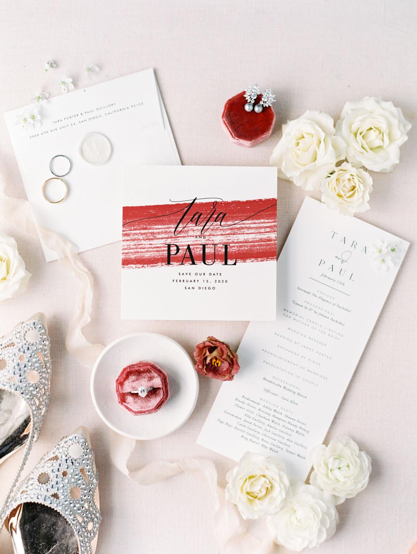Modern wedding invitation with burgundy brush stroke styled with rings, earrings, and Badgley Mischka flats. Hotel Del Coronado Wedding on film by Cavin Elizabeth.