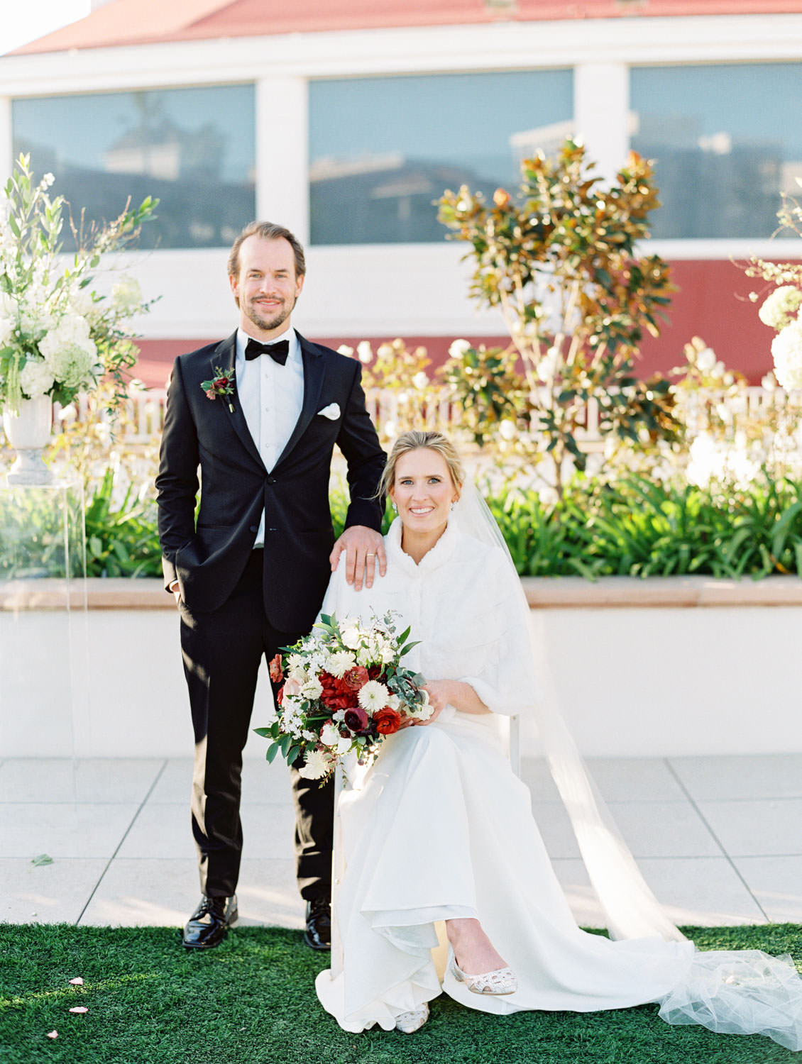 Bride and groom portrait with bride sitting down and groom standing. How to pose at your wedding when you have an injured leg. Hotel Del Coronado wedding on film by Cavin Elizabeth.