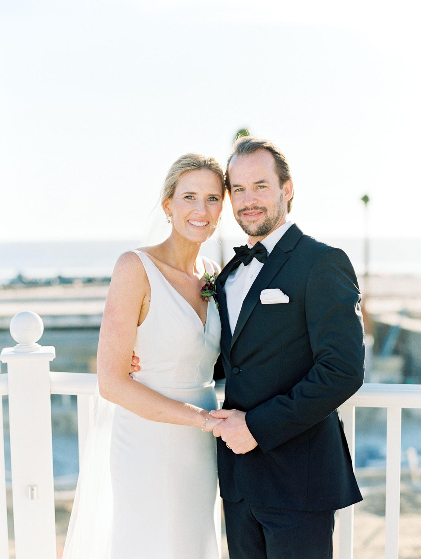 Bride and groom on a patio with ocean view. Hotel Del Coronado wedding on film by Cavin Elizabeth.