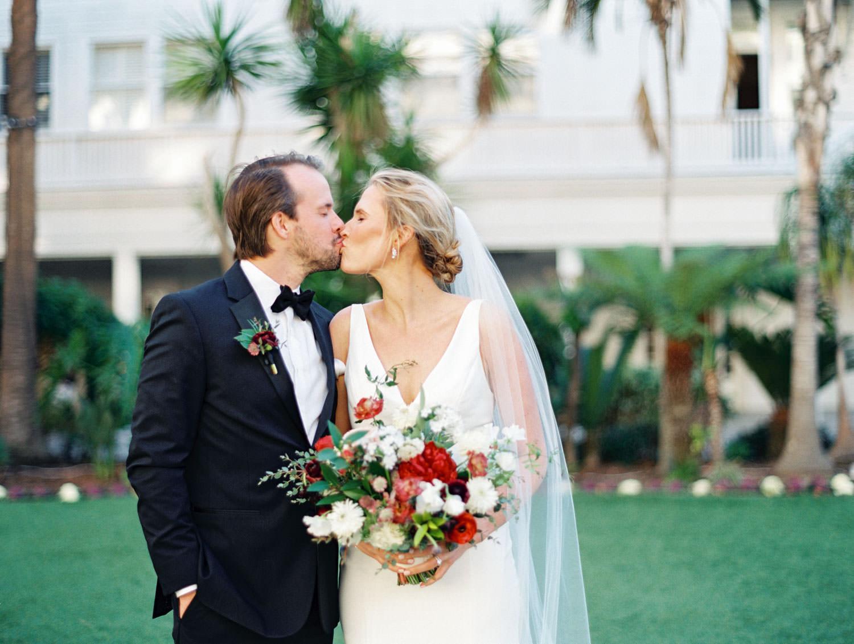 Bride and groom kissing. Bouquet with burgundy, blush, white, and greenery. Hotel Del Coronado wedding on film by Cavin Elizabeth.