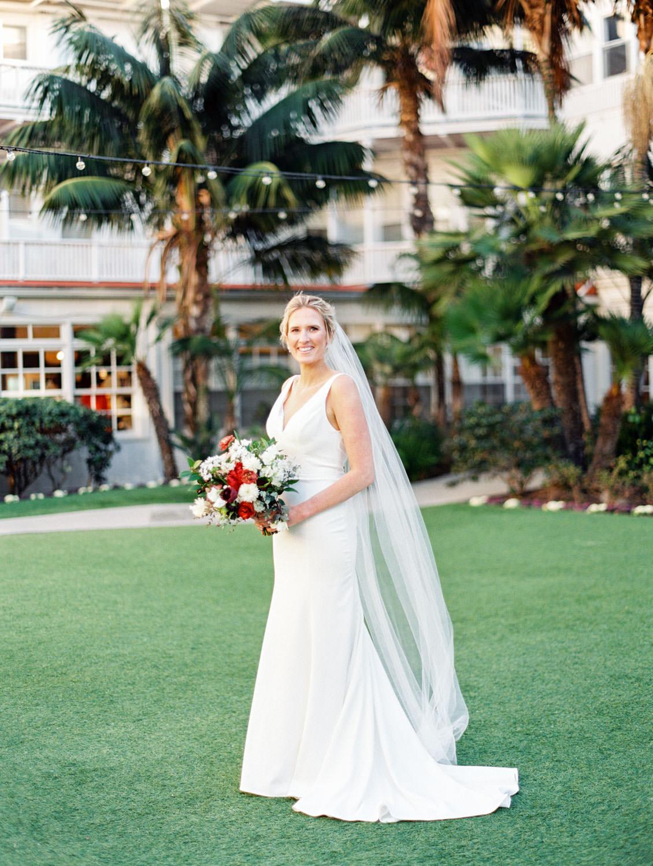 Bride in BHLDN Jenny Yoo wedding dress and long veil. Bridal bouquet with burgundy peonies, white flowers, and greenery. Hotel Del Coronado wedding on film by Cavin Elizabeth.