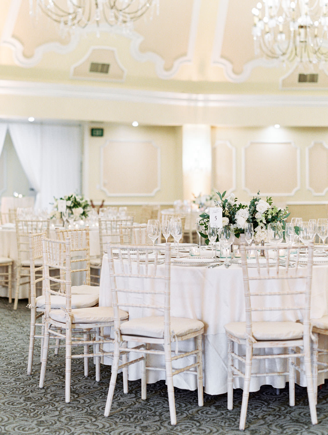 Ballroom round tables with white linens and chiavari chairs and ivory and green centerpieces. Hotel Del Wedding reception by Cavin Elizabeth
