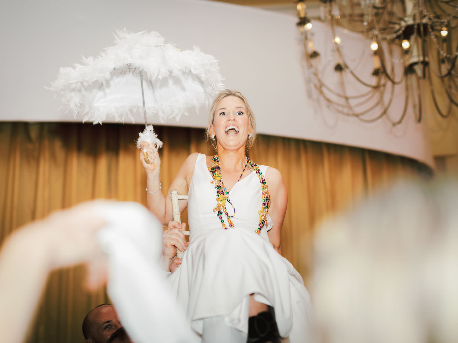 Bride held up on a chair during New Orleans second line with umbrellas and Mardi Gras beads. Hotel Del Wedding reception by Cavin Elizabeth.