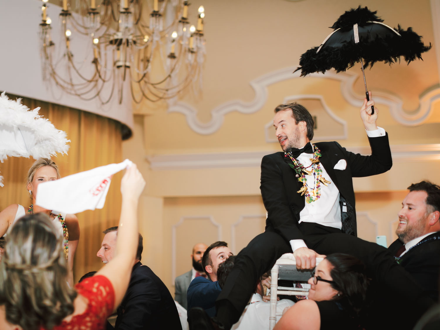 Groom held up on a chair during New Orleans second line with umbrellas and Mardi Gras beads. Hotel Del Wedding reception by Cavin Elizabeth.