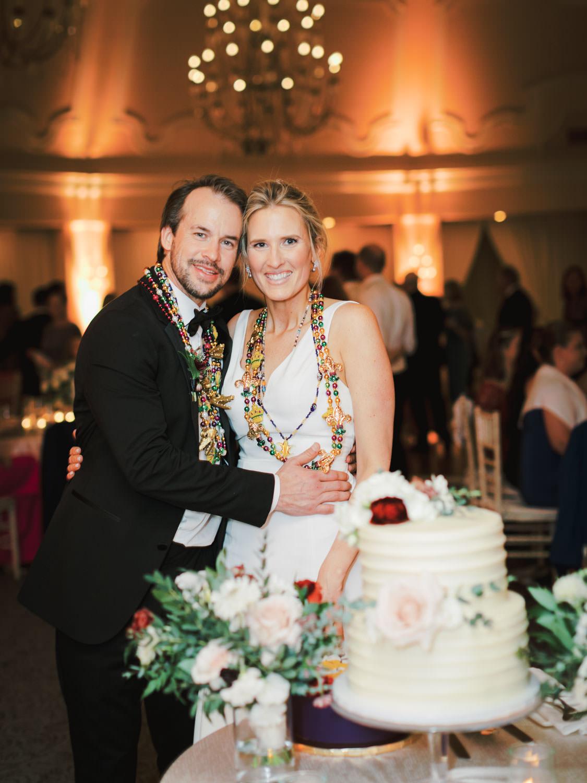 Bride and groom cake cutting wearing Mardi Gras beads. Hotel Del Wedding reception by Cavin Elizabeth.