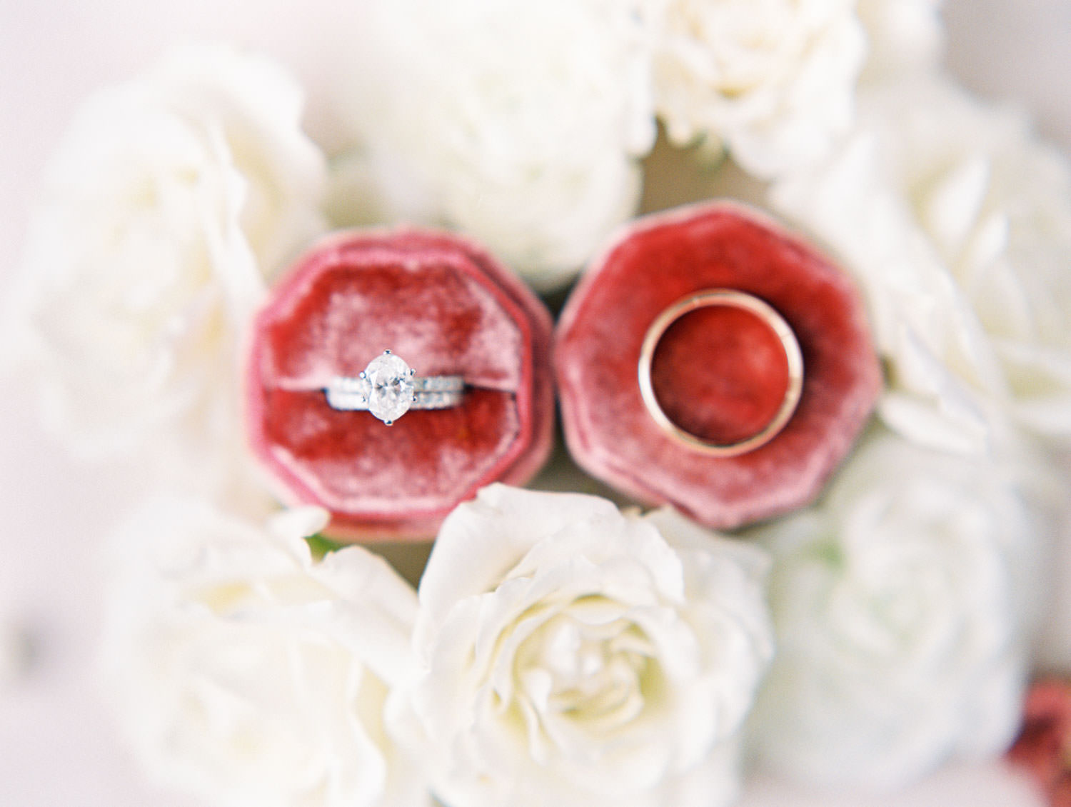 Engagement ring and wedding bands in burgundy velvet octagon ring box.